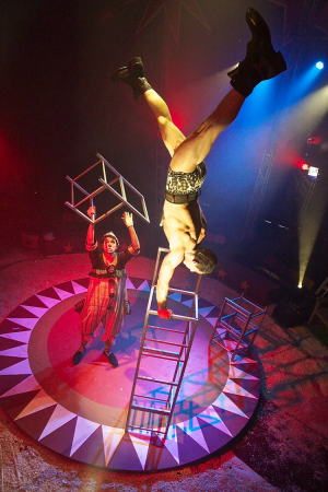 The Strongman Gilberto Salgueiro Filho balances on top of a tower of chairs in the Big Top tent, as Clown Jonathan De Lima Sbano looks on in The Story of the Moon